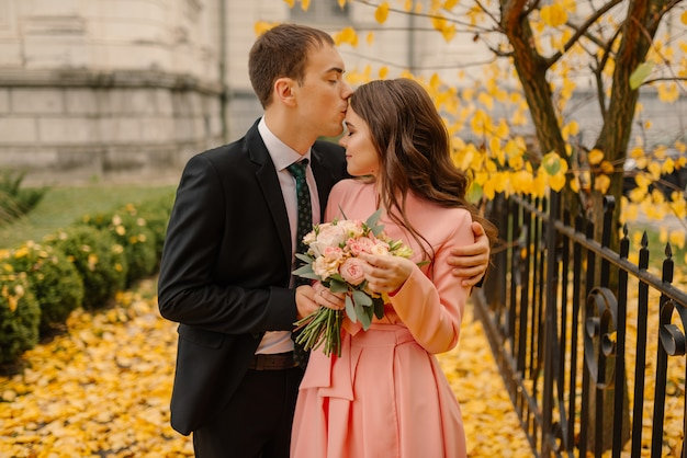 Happy young newly married wedding couple on walk in golden yellow fall autumn park near vintage atmosphere gothic cathedral.