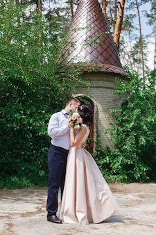 Happy young newlyweds hugging and kissing on their wedding day. bride and groom walk at the wedding in nature. romantic moment on the date. couple in love outdoors