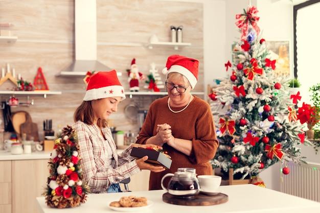 Счастливая молодая племянница смотрит на рождественскую подарочную коробку от бабушки