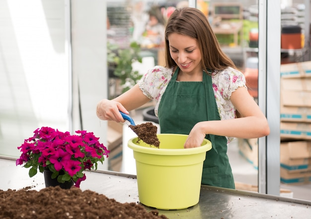 Happy young nursery worker potting a petunia