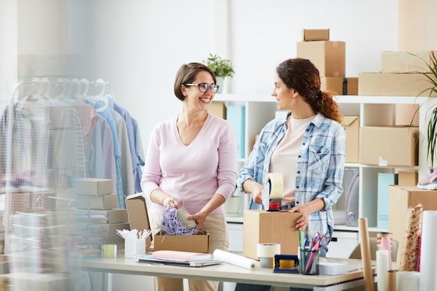 オンラインクライアントの注文の準備と梱包を行う幸せな若いオフィスマネージャー