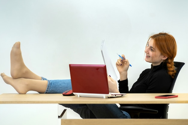 Happy young office worker woman sitting relaxed with feet on table behind working desk with laptop computer