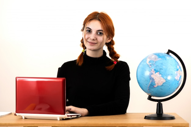 Happy young office worker woman sitting behind working desk with laptop computer, cell phone, notebook and geographic globe of the world.