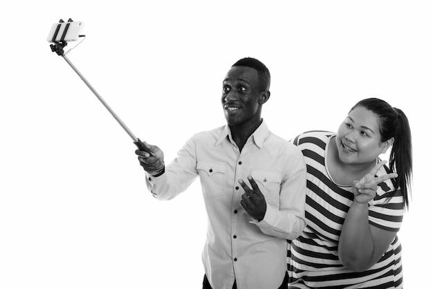 自撮り棒で電話と一緒に自分撮りをしているカップルとして幸せな若い太りすぎのアジアの女性と若いアフリカ人男性