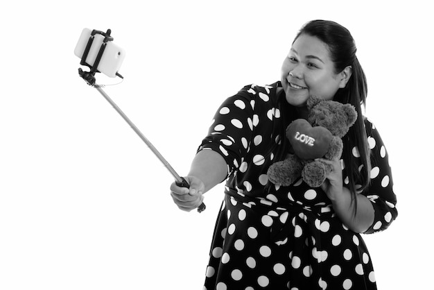 Happy young overweight asian woman holding teddy bear