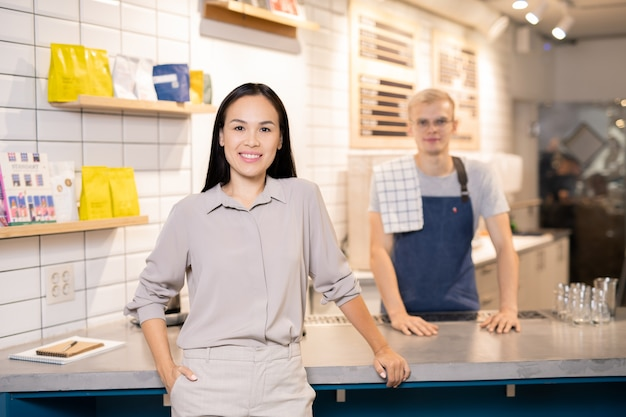 Happy young owner of restaurant or cafe standing by counter in front of camera with waiter in uniform on background