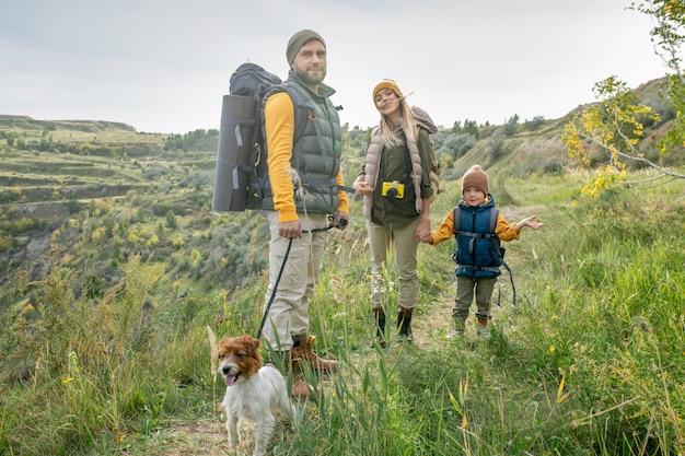 草や木々に覆われた山々との旅行中に歩道に立っている暖かいカジュアルウェアで幸せな若い親とそのかわいい幼い息子