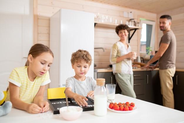 朝食後、キッチンに立って子供たちが遊んでいるのを見ながら、カジュアルウェアを着た幸せな若い親がその日の計画について話し合っています