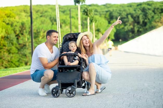 행복한 젊은 부모 엄마와 아빠는 여름에 공원에서 유모차를 타고 아기와 함께 지는 태양 아래 걷고 있고 먼 곳을 가리키며 즐겁게 웃고 있습니다