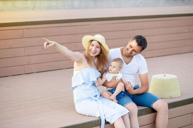 행복한 젊은 부모 엄마와 아빠는 아기 아들과 함께 제방이나 공원에서 걷습니다.