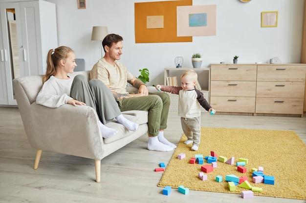 ソファに座って、部屋でカラフルなブロックで遊んでいる彼らの幼い息子を見ている幸せな若い親