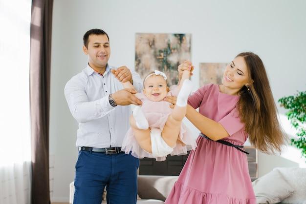Счастливые молодые родители качают свою дочь на руках