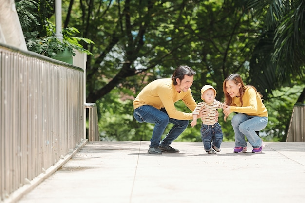 逃げようとしている子供を捕まえようとしている幸せな若い親