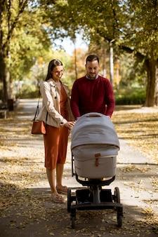 Счастливые молодые родители гуляют в осеннем парке и водят ребенка в детской коляске