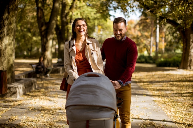 Happy young parents walking in the park and driving a baby in baby carriage