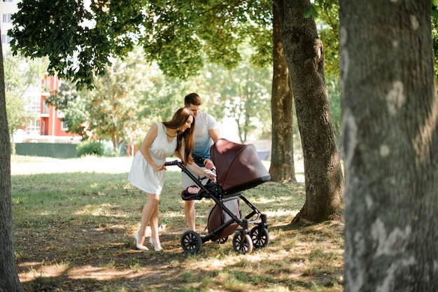 Happy young parents walking in park with baby carriage
