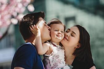 Счастливые молодые родители с маленькой дочерью стоят под цветущим розовым деревом