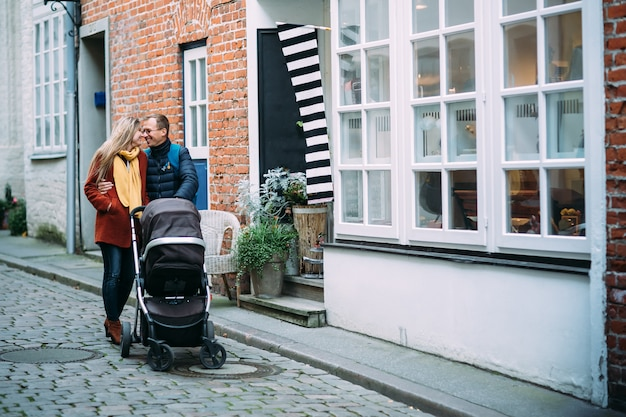 Happy young parents with baby stroller in the street of lubeck (germany)