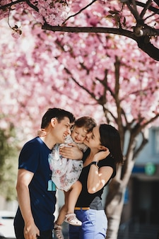 Happy young parents with a little daughter stand under blooming pink tree outside