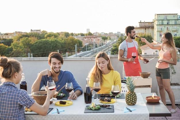 屋外のバーベキューパーティーで一緒にワインを食べたり飲んだりする幸せな若者たち-シェフの男の顔に焦点を当てる