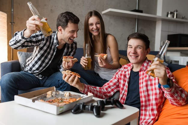 Happy young people eating pizza, drinking beer, having fun, friends party at home, hipster company together, two men one woman, smiling, positive, relaxed, hang out, laughing,
