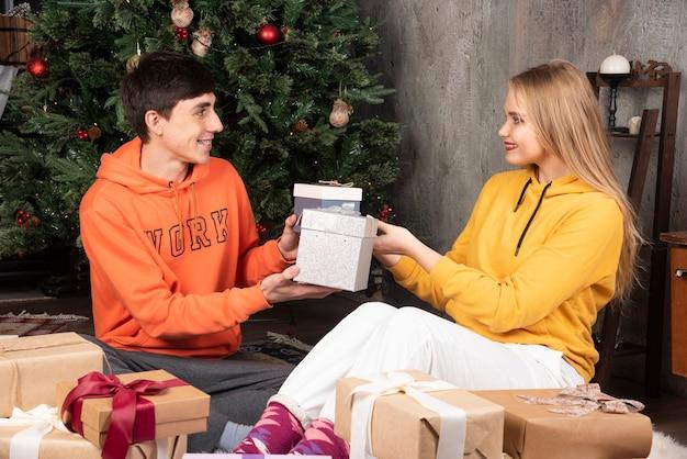 幸せな若者たちは、クリスマスツリーの近くでお互いに贈り物をします。