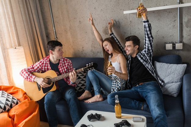 Счастливые молодые люди веселятся, вечеринка друзей дома, хипстерская компания вместе, двое мужчин и одна женщина, играют на гитаре, улыбаются, позитивно, расслаблены, пьют пиво