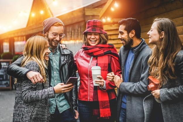 Счастливые молодые люди веселятся вместе из старинной пекарни - друзья millennials смеются, пьют кофе и используют смартфон - концепция путешествий и отдыха - сосредоточьтесь на лице девушки в центре