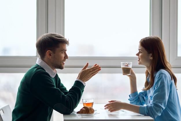 Счастливые молодые люди в кафе и чашечку чая влюбленной пары