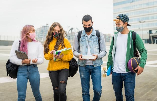 Covid-19 전염병 동안 야외에서 만나고 얼굴 마스크를 착용하는 행복한 젊은이들
