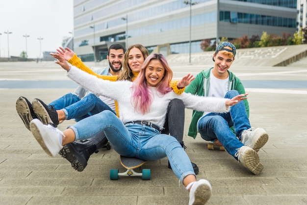 Happy young people meeting outdoors. group of cheerful teenagers having fun