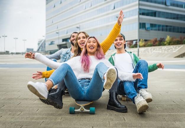 幸せな若者が屋外で会う。楽しんでいる陽気なティーンエイジャーのグループ
