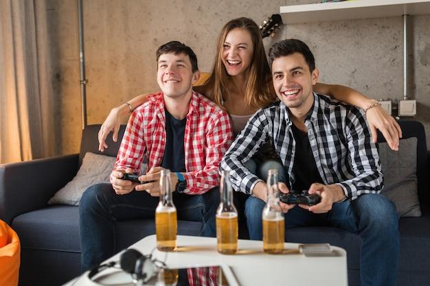幸せな若者、ビデオゲームをプレイ、楽しい、自宅での友人パーティー、ヒップな会社、2人の男性、一人の女性、笑顔、前向き、リラックス、感情的、笑い、競争
