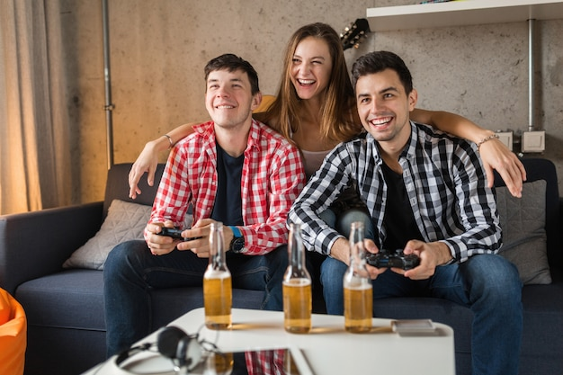 Happy young people playing video games, having fun, friends party at home, hipster company together, two men one woman, smiling, positive, relaxed, emotional, laughing, competition