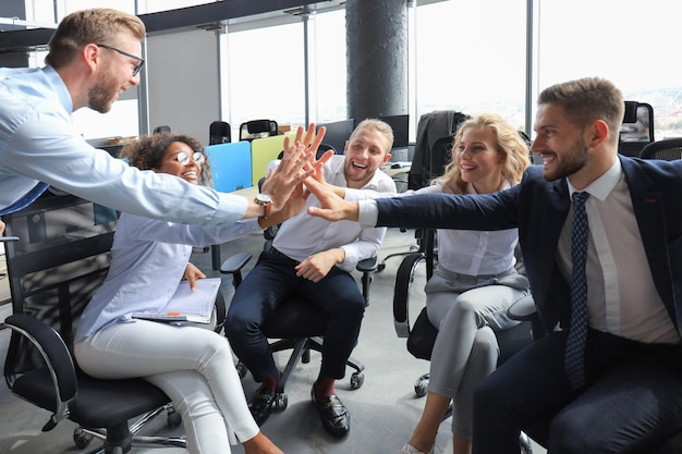 Happy young people sitting in office and giving high five to their colleagues.