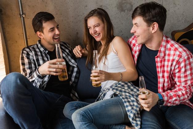 Giovani felici seduti sul divano, bere birra, chiudere le mani tostare, divertirsi, festa a casa di amici, compagnia hipster insieme, due uomini una donna, sorridente, positivo, rilassato, uscire, ridere