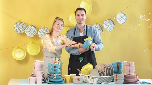 Счастливые молодые люди, стоящие за столом и смотрящие в камеру, моют грязную посуду. концепция домохозяйки