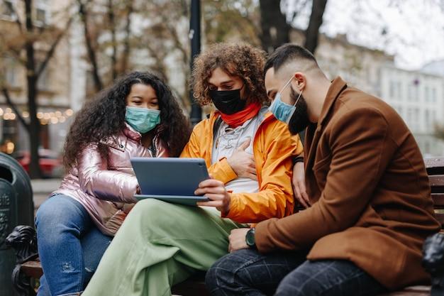 新鮮な空気に自由な時間を過ごしながら、デジタルタブレットを使用して幸せな若者。屋外の木製ベンチに座っている医療マスクを身に着けている多文化の人々。