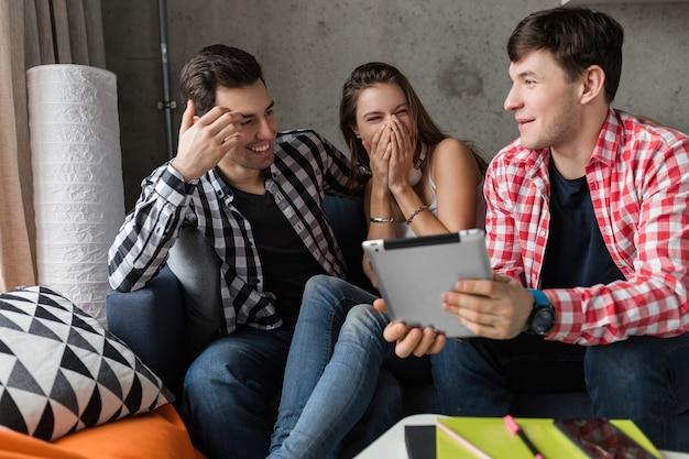 Счастливые молодые люди, использующие планшет, студенты учатся, развлекаются, вечеринка друзей дома, хипстерская компания вместе, двое мужчин, одна женщина, улыбка, позитив, онлайн-образование