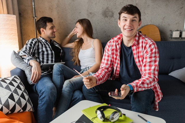 Giovani felici che utilizzano tablet, studenti che imparano, divertirsi, amici fanno festa a casa, compagnia hipster insieme, due uomini una donna, sorridente, positivo, educazione online, uomo che tiene il telefono