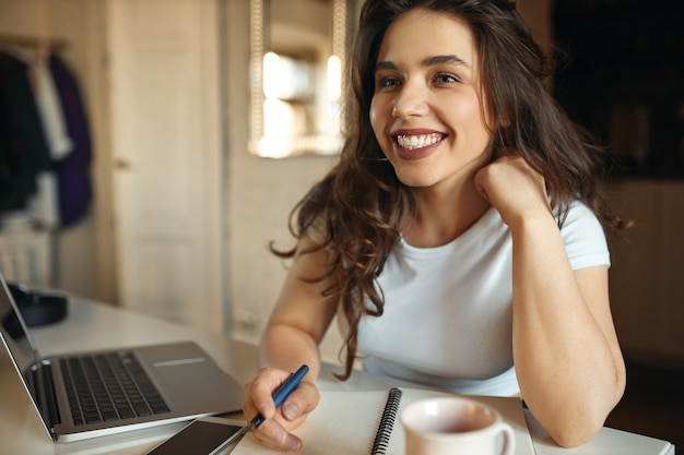 Счастливый молодой плюс размер женщина делает заметки в своей тетради, используя беспроводное подключение к интернету на ноутбуке