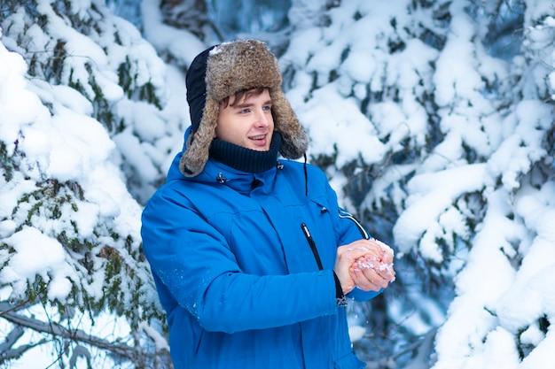 Счастливый молодой позитивный человек играет в снежки в зимнем снежном лесу