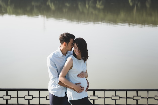 Happy and young pregnant couple hugging in nature at the lake
