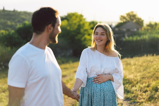 Happy and young pregnant couple in outdoors