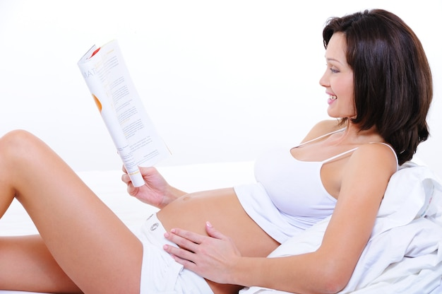 Счастливая молодая беременная женщина читает журнал