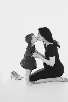 Happy young pregnant mum kissing her little child and hugs with her isolated on white background