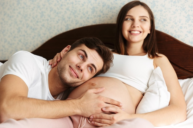 Happy young pregnant wife lying in bed with her husband