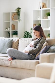リビングルームのソファに足を組んで座って、彼女の子宮の中で赤ちゃんと話しているカジュアルな服装で幸せな若い妊婦