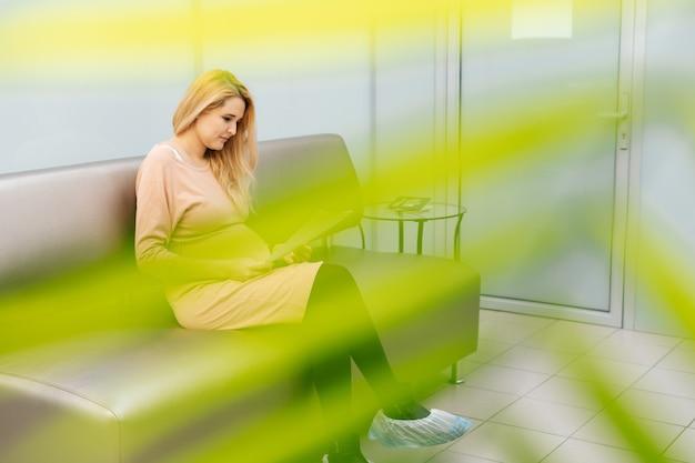 幸せな若い妊婦は、婦人科医に会うのを待っている病院の廊下に座っています
