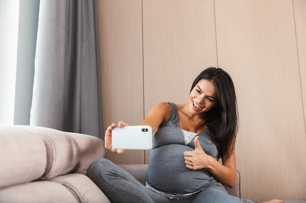 Happy young pregnant woman sitting on a couch at home, taking a selfie
